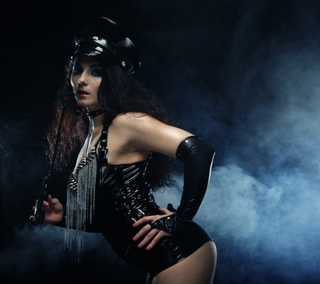 Sexy brunette woman mistress holding whip,over dark background