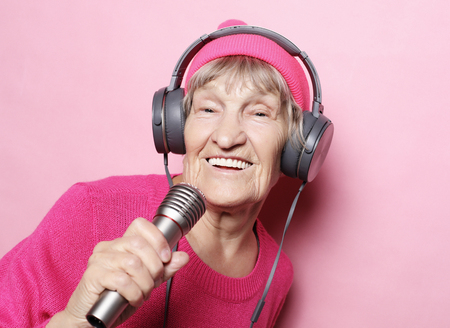 Happy grandmother with headphones and microphone over pink background, funny singer