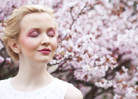 Portrait of a beautiful young blond woman on a background of pink cherry blossoms in spring Stok Fotoğraf