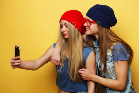 two young hipster girls friends  taking selfie over yellow background