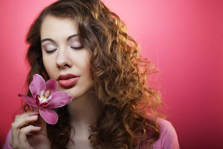 Beautiful happy woman with orchid flower over pink background