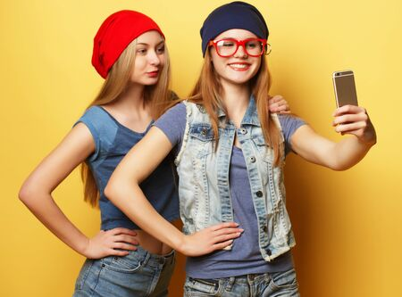 two young hipster girls friends  taking selfie over yellow background Фото со стока - 129822434