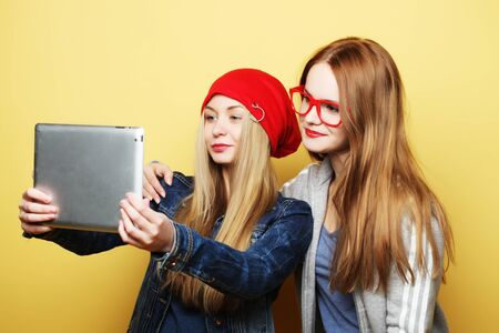 two hipster girls friends taking selfie with digital tablet 스톡 콘텐츠 - 129822435
