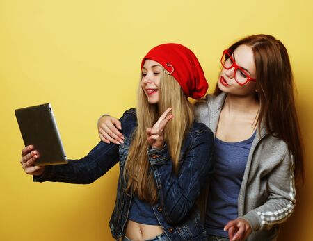 two hipster girls friends taking selfie with digital tablet 스톡 콘텐츠