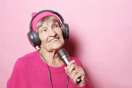 lifestyle and people concept: Funny old lady listening music with headphones and singing with mic