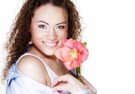 Beautiful young  woman with pink flower over white background