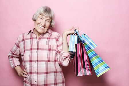 Happy grandmother with shopping bags over pink background. Lifestyle and people concept.