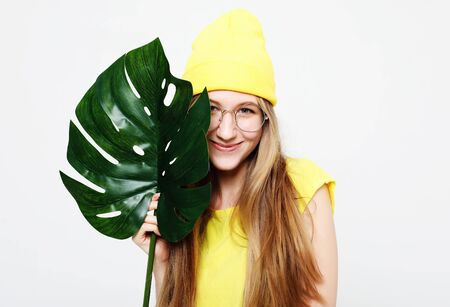 lifestyle, emotion  and people concept: Smiling beautiful woman behind leaf