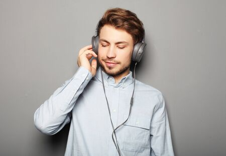 Handsome young man wearing headphones and listening to music.