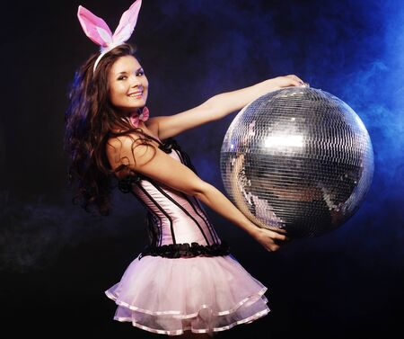 Young sexy bunny-girl with disco ball over dark background