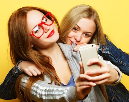 Two teenage girls friends in hipster outfit make selfie on a phone