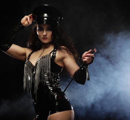 Sexy mujer joven en pantalones cortos de cuero, lencería negra y gorra negra uniforme sobre un fondo oscuro. Amante Caliente.