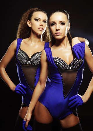 two striptease girls over dark background