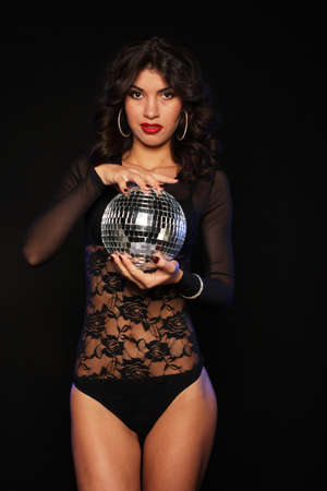 young brunette woman wearing lingerie with disco ball, posing in studio