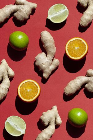 Ginger, Oranges, Limes on red background. Antioxidant Food.