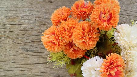 insists: plastic orange and white flower on old wooden background,Verdolaga
