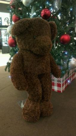 beside: Brown bear standing beside a Christmas Tree