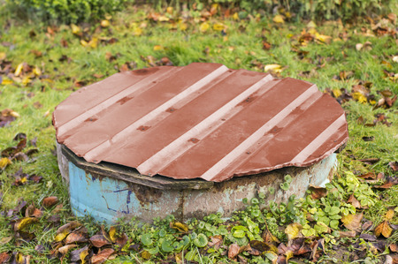 Old rustic concrete drain well with painted metallic cup in autumn Stock Photo