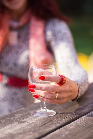 Females hand with red long nails holding a wine glass on a wooden table