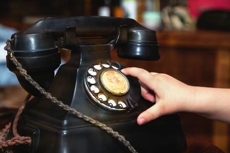 Child finger turning an old black vintage phone .Close up.