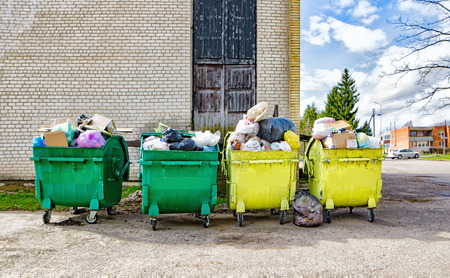 Green and yellow containers with garbage near the house in the street Stok Fotoğraf