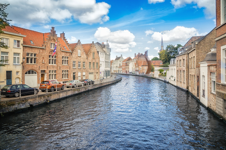 Bruges canal, buildings, church and a metal wire installation on a sunny day. Belgium Stock Photo