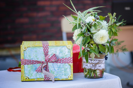 Flowers bouquet and a gift with ribbon  on the table