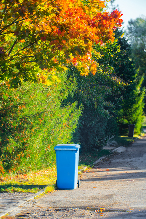 Blue container with garbage near the house in the street in autumn Stok Fotoğraf