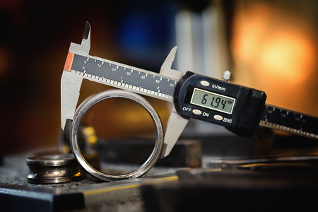 Electronic calipers on an old bearing detail. Close up.