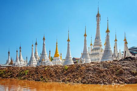 White temples near water body in Myanmar. Asia. Stockfoto