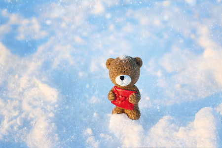Teddy bear with a letter in the snow on a winter day. Stock Photo