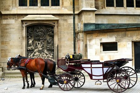 girth: horses and coach on a street with old building in background