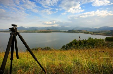 stabilization: Tripod of landscape photographer on a meadow by the lake in evening lake