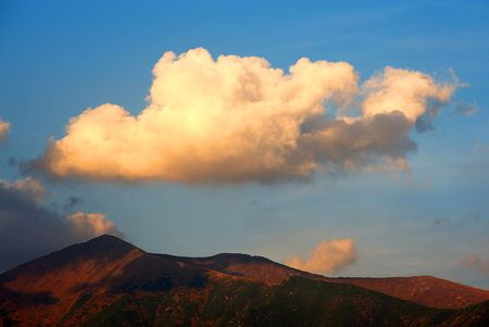 red evening: Gorgeous cloud above a mountain in red evening light Stock Photo
