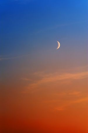 deep orange: Waxing Crescent Moon on sky colored by sunset from deep orange to blue Stock Photo