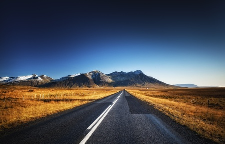 Road in autumn country with mountains on horizon and blue sky photo
