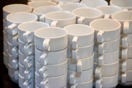 White cups for tea piled on table with plates for coffee-break  photo