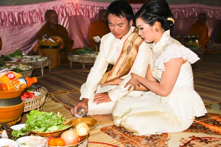 UBON RATCHATHANI - JANUARY 27  Bride and groom gets married during a traditional Thai isan buddhist wedding on January 27, 2013 in Ubon Ratchathani, Thailand Редакционное