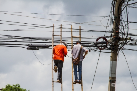 Employee works on power line on a sunny day with blue skies  He is wearing safety equipment including belt and neon vest