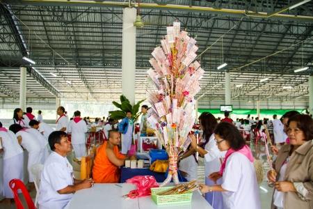 donates: UBONRATCHATHANI, THAILAND - JULY 24  Unidentified Thai Buddhist donates banknote in donation tree on July 25, 2013 in Ubonratchathani, Thailand on Visakha Bucha day  Visakha Bucha is the Buddha s birthday, enlightenment, and nirvana day