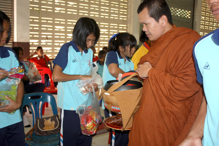 thai student: Monk receiving food and items offering from Thai student