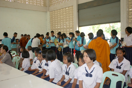 endow: Monk receiving food and items offering from Thai student