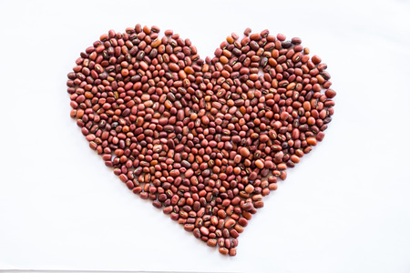 Heart of red beans on a white background photo
