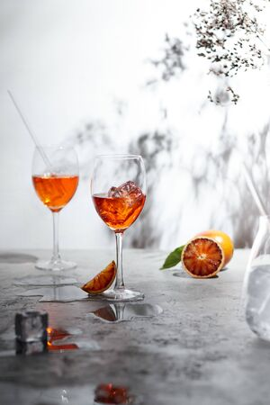 Refreshing    cocktails with straws, ice cubes and sliced orange on a grey background- summer day sunlight shadows Stockfoto