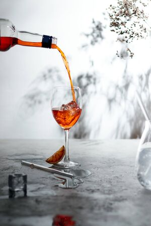 Refreshing   cocktails with straws, ice cubes and sliced orange on a grey background- summer day sunlight shadows
