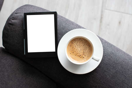 Mockup Ebook on soft modern armchair With Blank White Screen, to replace your design. Cup of Coffee for cozy atmosphere reading. Paste your book cover here