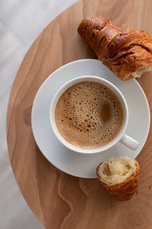 Modern french breakfast Top view. White cup of hot coffee with fresh baked croissant on the round wooden table