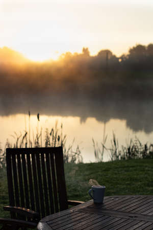 sunrise ritual, breakfast outdoor, drinking tea or coffee early morning by the lake or pond