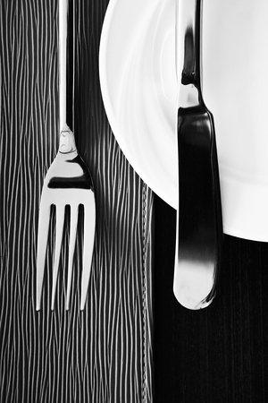 Knife, fork and plate on texture  background