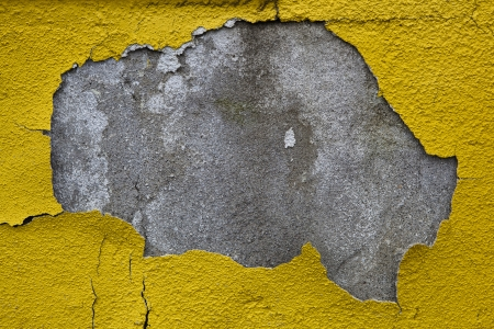 Old wall with dirty broken weathered yellow paint photo